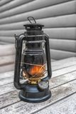 Old fashioned lantern on the wooden table. Vintage style metal lamp outdoor. Old fashioned lantern on the wooden table. Vintage style metal lamp outdoor Royalty Free Stock Photo