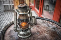 Old fashioned lantern on the wooden table. Vintage style metal lamp outdoor. Old fashioned lantern on the wooden table. Vintage style metal lamp outdoor Royalty Free Stock Images