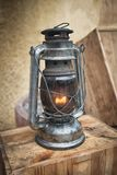Old fashioned lantern on the wooden table. Vintage style metal lamp outdoor. Old fashioned lantern on the wooden table. Vintage style metal lamp outdoor Stock Image