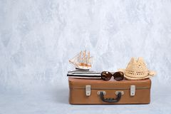 Old fashioned leather travel bag with summer marine accessories: glasses, straw beach hat, toy sailboat on grey background. Banner. Mockup with copy space stock photos