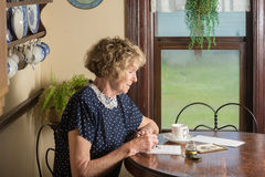 Old fashioned letter. In a historical scene from the 1930's or 1940's, an attractive elderly woman writes a letter as she sits at a table by a royalty free stock photo