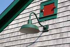 Old Fashioned Light. An old fashioned light fixture on the side of a wood shingled building stock photo