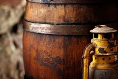 Old fashioned light kerosene lantern style oil lamp and barrels.closeup royalty free stock photo