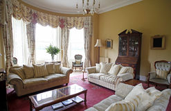 Old fashioned living room. With sofas and coffee table and big bay window Royalty Free Stock Images