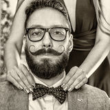 Old-fashioned man with a beard and curled mustache. Woman with manicure straightens a bow tie to old-fashioned man in glasses with a beard and curled mustache Royalty Free Stock Photography