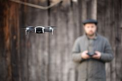 Old fashioned men from village mastering to fly drone, basics of remote control stock photo