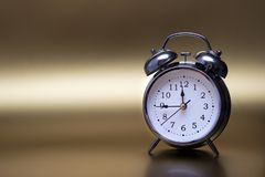 Old fashioned metal alarm clock on a gold background. royalty free stock image