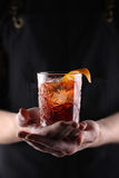 Old fashioned Negroni cocktail in hand on the black background Royalty Free Stock Photo