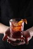 Old fashioned Negroni cocktail in hand on the black background Stock Images