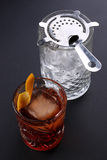 Old fashioned Negroni cocktail near glass with ice on the black background Stock Photo