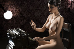 Old fashioned of nude woman typing Stock Images
