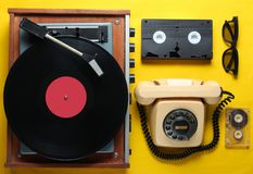 Old-fashioned objects. On yellow background. Retro style, 80s, pop culture. Top view. Vinyl player, rotary phone, video, audio tape royalty free stock photo