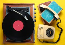 Old-fashioned objects. On yellow background. Retro style, 80s, pop culture. Top view. Vinyl player, rotary phone, old books royalty free stock photography