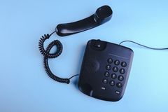 Old fashioned phone on blue background. Close up stock photos