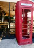 Old fashioned phone booth. Chipped red paint and missing glass on this antique phone booth in front of a restaurant patio Royalty Free Stock Image