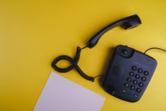Old fashioned phone on yellow background with blank paper and pen. Close up royalty free stock photography