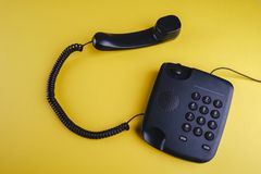 Old fashioned phone on yellow background. Close up stock photos