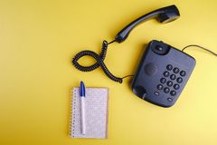 Old fashioned phone on yellow backgroundOld fashioned phone on yellow background with blank notebook and pen. Old fashioned phone on yellow background with blank royalty free stock photo