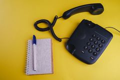 Old fashioned phone on yellow backgroundOld fashioned phone on yellow background with blank notebook and pen. Old fashioned phone on yellow background with blank royalty free stock photography
