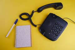 Old fashioned phone on yellow backgroundOld fashioned phone on yellow background with blank notebook and pen. Old fashioned phone on yellow background with blank royalty free stock image