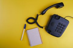 Old fashioned phone on yellow backgroundOld fashioned phone on yellow background with blank notebook and pen. Old fashioned phone on yellow background with blank stock photography