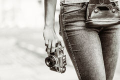 Old fashioned picture of a girl holding a retro camera. In the city stock images