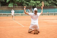 Old-fashioned players after winning tennis match. On court stock photo