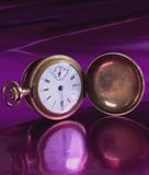 Old-fashioned pocket watch. With purple backdrop and reflection Royalty Free Stock Photography