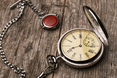 Old fashioned pocket watch with chain on rough wood Stock Images