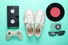 Old-fashioned objects. Old fashioned pop culture attributes from 80s on mint color background. Old sneakers, gamepad, audio cassette, videotape, vinyl plates, 3d royalty free stock images