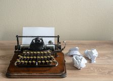 Old antique portable typewriter with screwed up paper on desk. Old fashioned portable typewriter with non qwerty keys and screwed up paper on desk Stock Image
