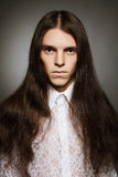 Old fashioned portrait of a long-haired boy. Over dark gray background. Vintage style. studio shot stock photography