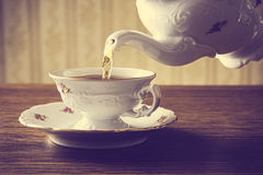 Old-fashioned pouring tea to cup on old wallpaper background Stock Photo