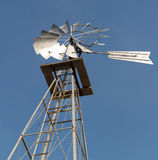 Old Fashioned Power Windmill. Angled and close up shot from the ground of an old fashioned power windmill against a clear blue sky Royalty Free Stock Photo