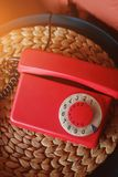 Old-fashioned red phone in beautiful retro interior, close-up, toned.  stock photography