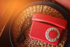 Old-fashioned red phone in beautiful retro interior, toned.  royalty free stock photography