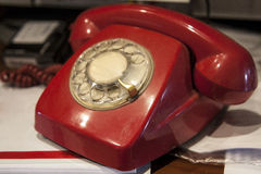Old Fashioned red phone over home desk Royalty Free Stock Photos
