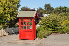 Old-fashioned red telephone booth in public garden Royalty Free Stock Photos