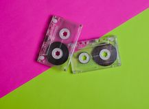Old-fashioned retro cassettes on a pink green neon background. Top view.  royalty free stock images
