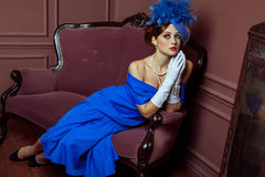 Old Fashioned retro great britain style photography. Beautiful young caucasian model in blue dress and fashion makeup and hat posing sitting on the artificial Stock Images