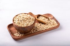 Old fashioned rolled oats. In a wooden bowl on white wooden table stock photography
