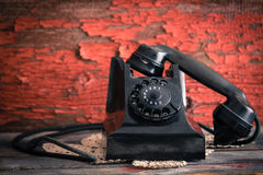 Old-fashioned rotary telephone off the hook. Old-fashioned rotary telephone with the handset off the hook effectively blocking the line against a rustic wall royalty free stock photos