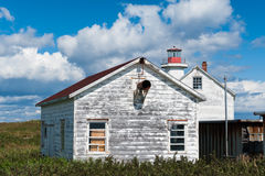 Old-fashioned rustic house and lighthouse Stock Image