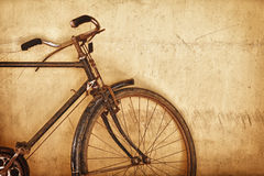 Old-fashioned rusty bicycle near the wall Royalty Free Stock Photo