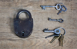 Old fashioned rusty lock with keys on wooden surface Royalty Free Stock Photography