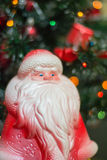 Old-fashioned Santa Claus toy. With blurred New Year Tree Royalty Free Stock Image