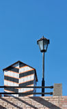Old-fashioned sentry box and street lamp. Wooden old-fashioned sentry box and street lamp over blue sky Royalty Free Stock Photography
