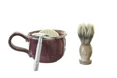 Old Fashioned Shaving Kit with Mug, Brush, and Raz. Shaving kit with mug, circular soap bar, shaving brush, and safety razor on white background Stock Photos