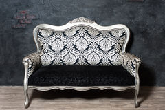 Old-fashioned sofa. Against the background of black wall Royalty Free Stock Photography