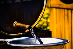 Old fashioned spigot. Water flowing from barrel via a rusty spigot. The norm in the 18 and 1900`s Stock Images